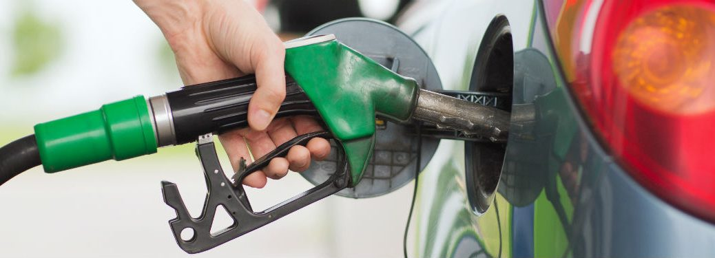 hand filling up a car with fuel