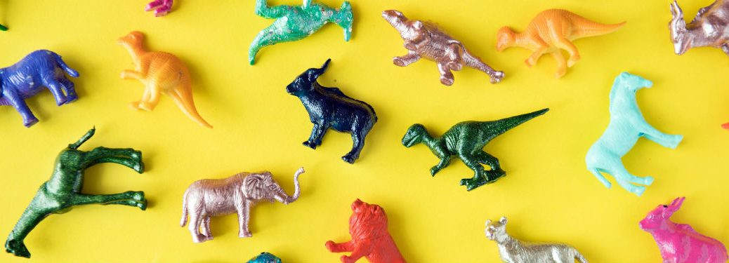 Group of dinosaur toys on yellow background