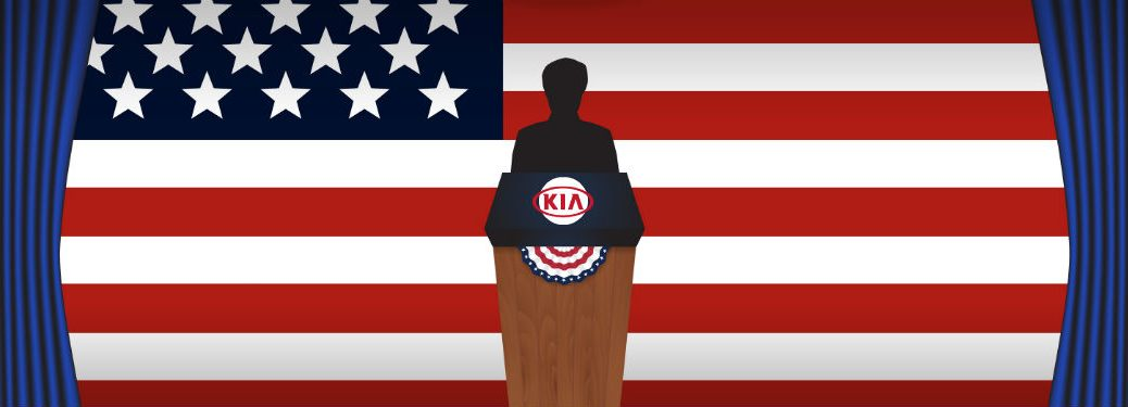 silhouetted person standing in front of podium with Kia logo on on it