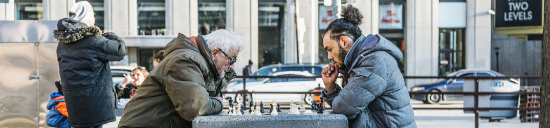 two men playing chess in the street