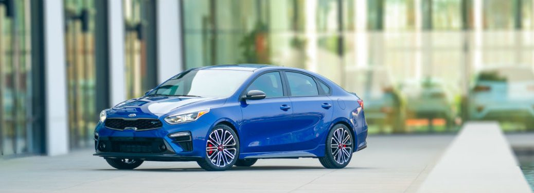 2020 kia forte gt in blue parked on road in front of glass garage