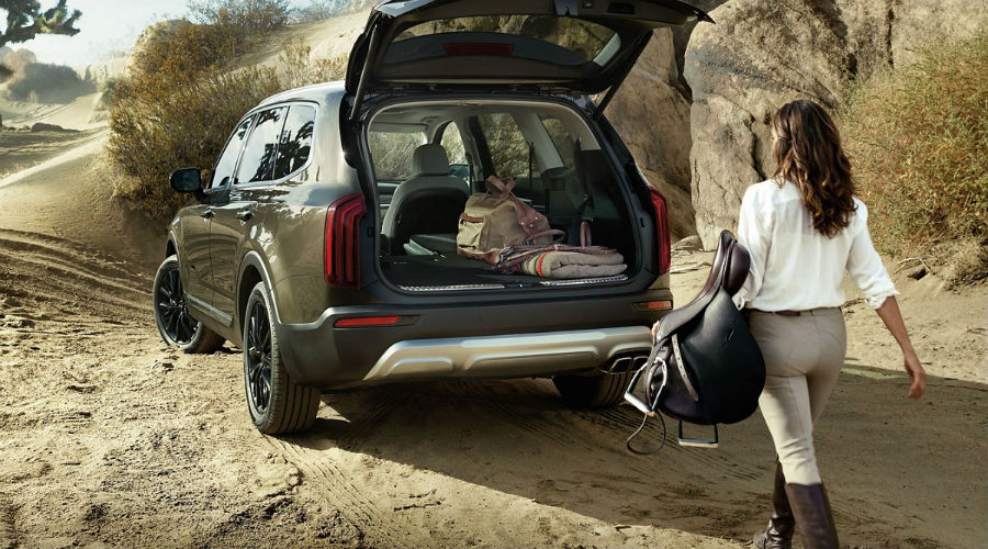 rear three quarters of 2020 kia telluride with person approaching and loading it