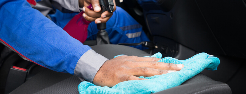 Hand cleaning interior of vehicle with cloth