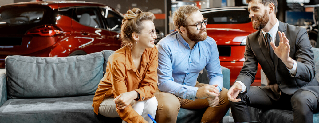 Couple sitting on couch with salesman
