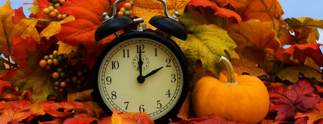 Alarm clock by pumpkin in fall scene