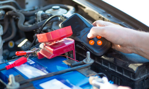 Closeup of person testing a car battery with testing tool