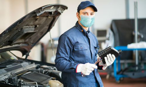 Car mechanic wearing mask in front of vehicle
