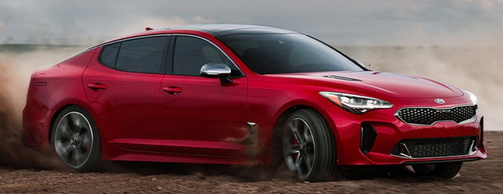 Red 2021 Kia Stinger driving on dirt