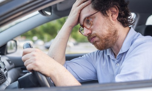 Male looking annoyed in vehicle driver's seat with hand on face