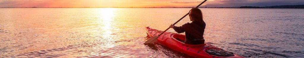 Person kayaking in front of sunset