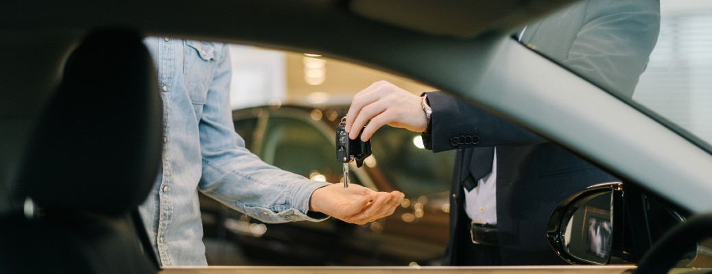 View through car window of two people exchanging keys
