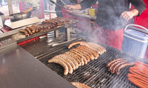 Person cooking brats on grill