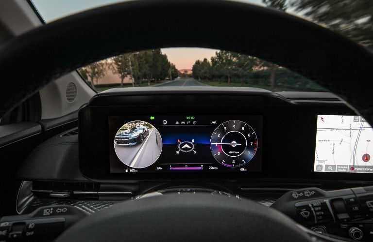 2022 Kia Carnival steering wheel and digital instrument cluster with the road ahead outside the windshield
