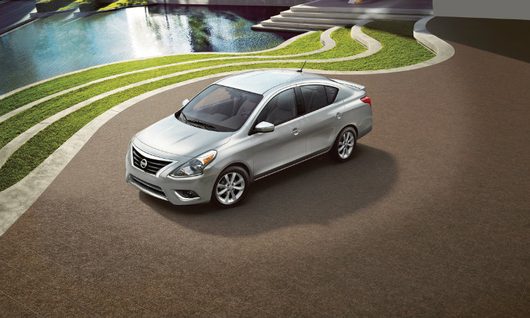 silver versa parked on concrete, near water and grass