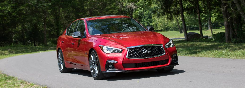 red infiniti q50 driving on small road