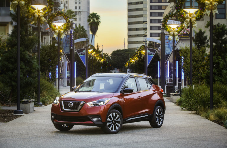 dark red nissan kicks in city