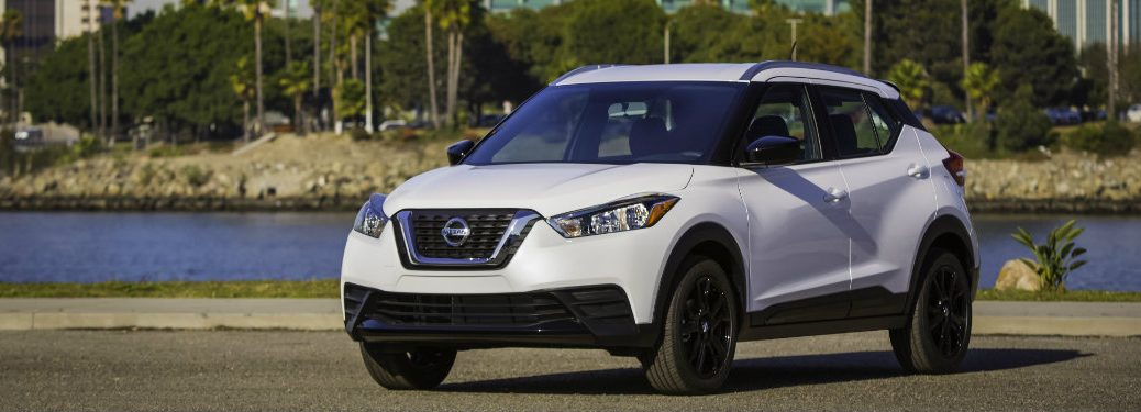 white nissan kicks near water and palm trees