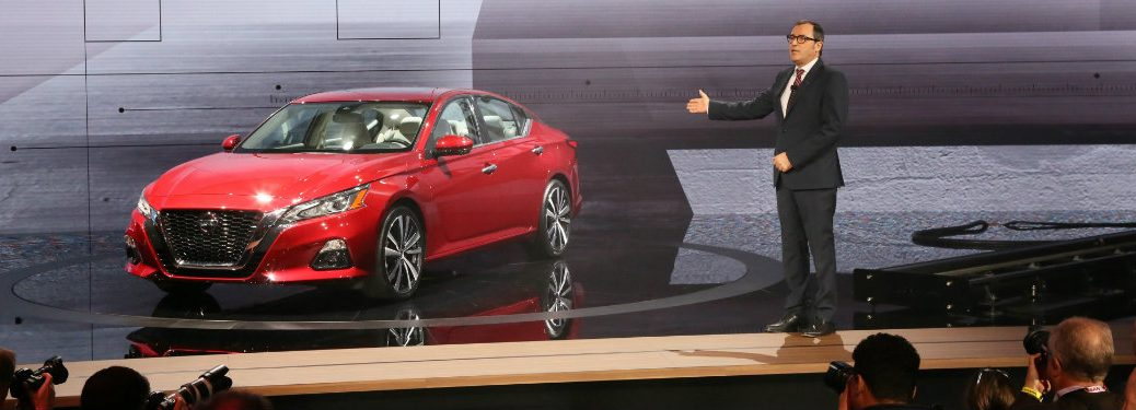 man on stage with red nissan altima