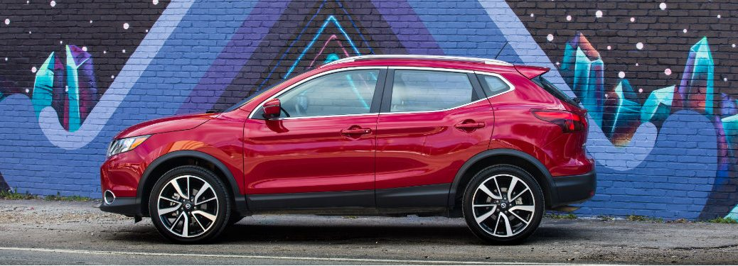 red nissan rogue sport parked by colorful mural