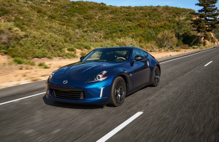 blue nissan 370z driving on country road
