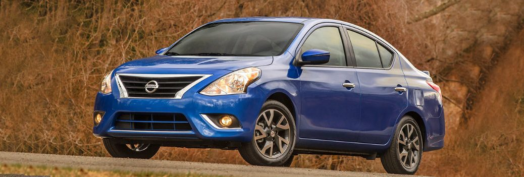 Nissan Versa blue parked by hill