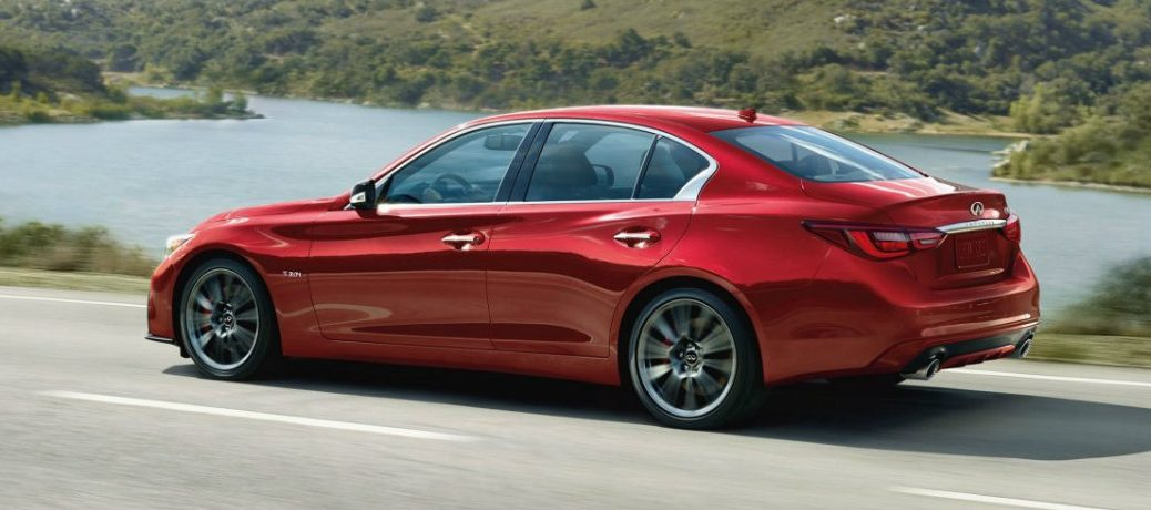 Exterior view of a red 2019 INFINIITI Q50 driving down a highway with a lake in the background