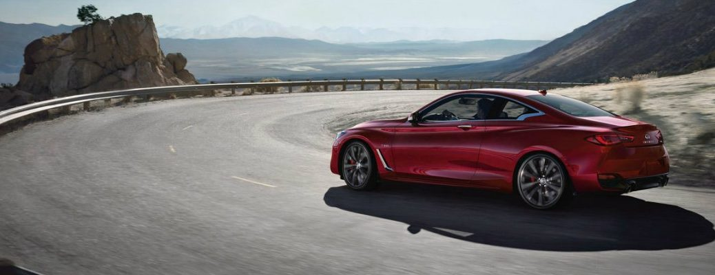 Exterior view of a red 2019 INFINITI Q60 driving around a curved highway