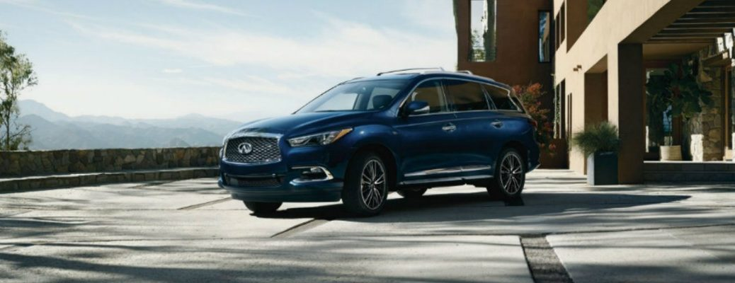 Exterior view of a blue 2019 INFINITI QX60 parked in the driveway of a beautiful home