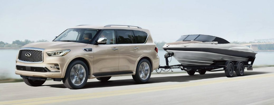 Exterior view of a tan 2019 INFINITI QX80 towing a boat down the highway