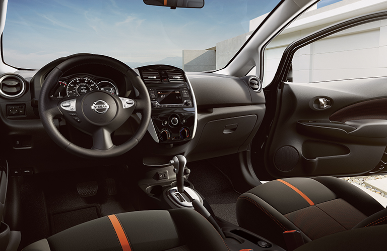 Interior view of the black steering wheel and touchscreen inside a 2019 Nissan Versa Note