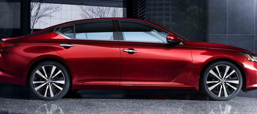 Exterior view of a red 2019 Nissan Altima parked outside an office building