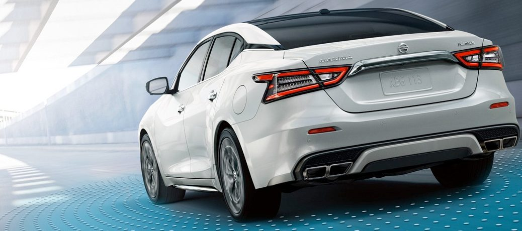 Exterior view of the rear of a white 2019 Nissan Maxima driving through a city tunnel
