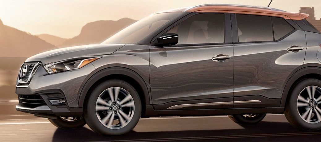Exterior view of a parked grey and orange 2019 Nissan Kicks with mountains in the background