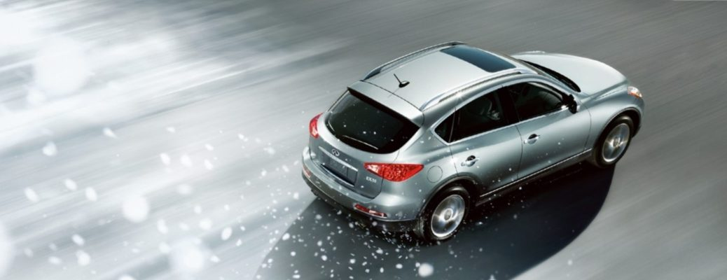 Arial shot of a silver INFINITI SUV driving down a road during heavy snowfall