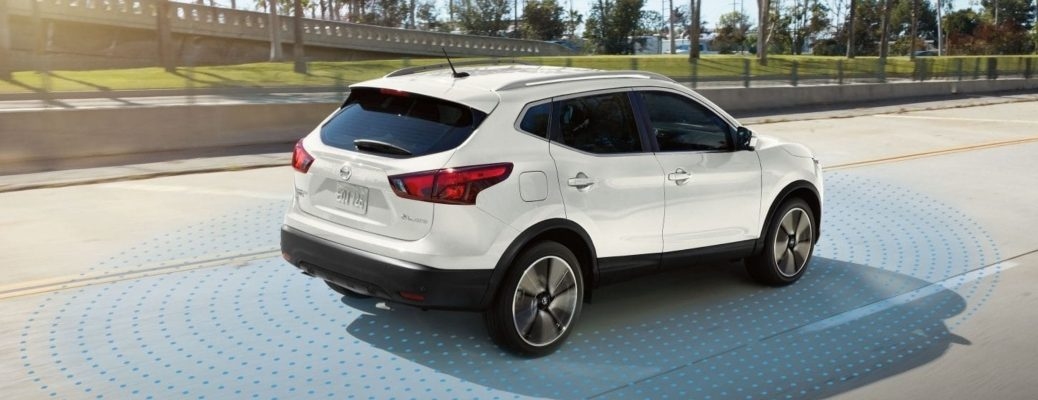 Exterior view of a white 2019 Nissan Rogue Sport driving down an empty road with a visual representation of the ProPILOT Assist sensors