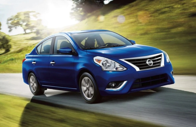 Exterior view of a blue 2019 Nissan Versa driving down a country road
