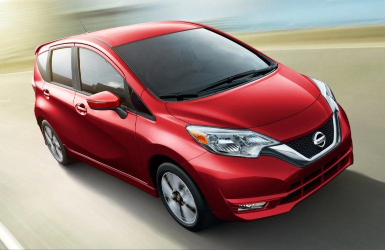 Exterior view of a red 2019 Nissan Versa Note driving down a country road