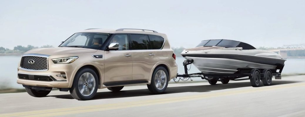 Exterior view of a tan 2019 INFINITI QX80 towing a boat down a country highway