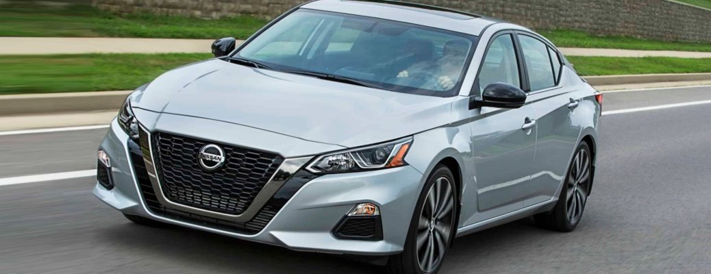 Exterior view of a silver 2019 Nissan Altima driving down a suburban street