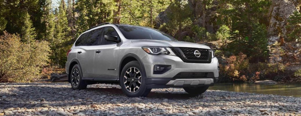 Exterior view of a silver 2019 Nissan Pathfinder Rock Creek Edition parked in the woods