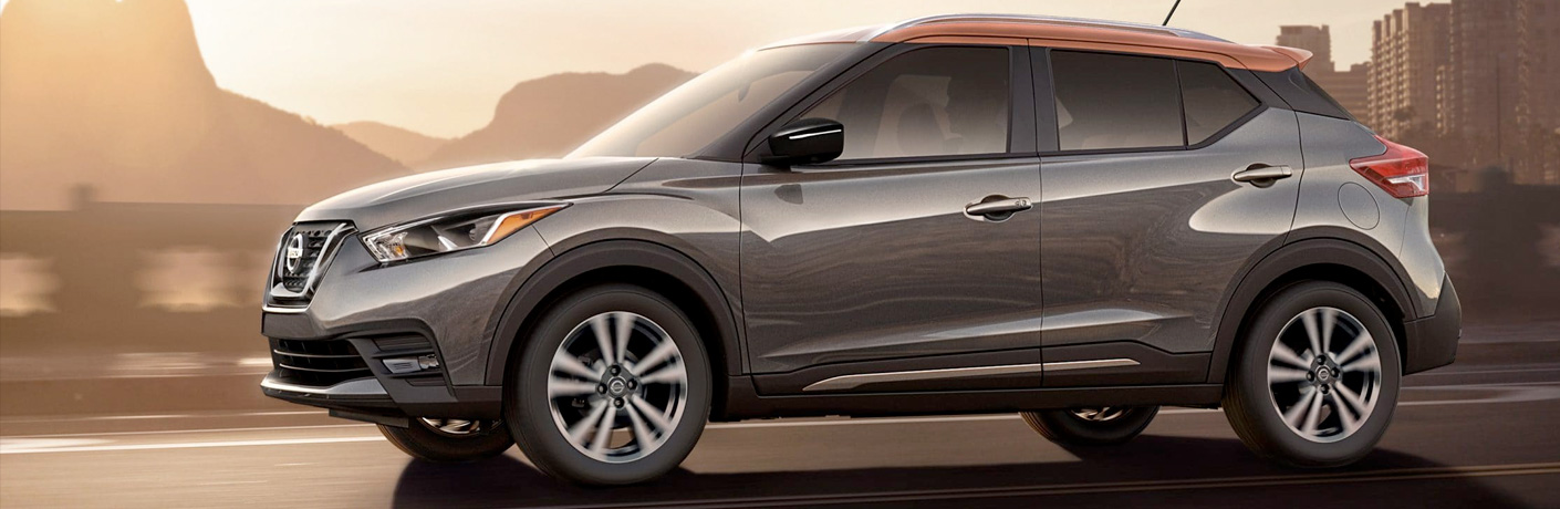 Exterior view of a gray and orange 2019 Nissan Kicks driving down a city street
