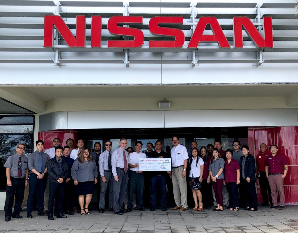 Photo of the staff at Nissan Guam presenting Catholic Social Services with a donation check