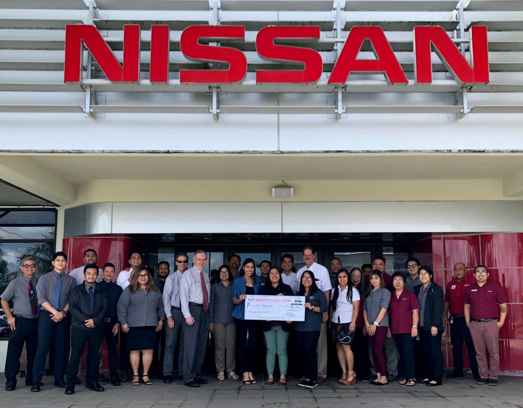 Photo of the staff at Nissan Guam presenting Guam Girl Scouts with a donation check