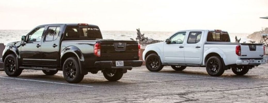 Exterior view of a black 2019 Nissan Frontier and a white 2019 Nissan Frontier