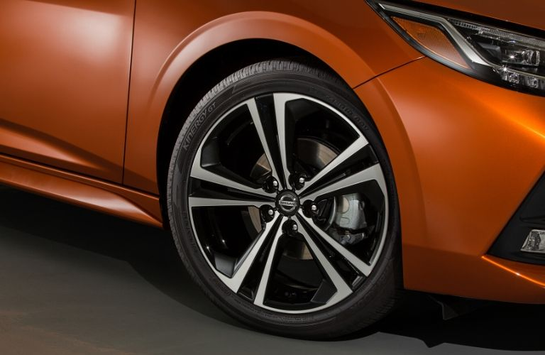 Exterior view of the driver's side front wheel on an orange 2020 Nissan Sentra