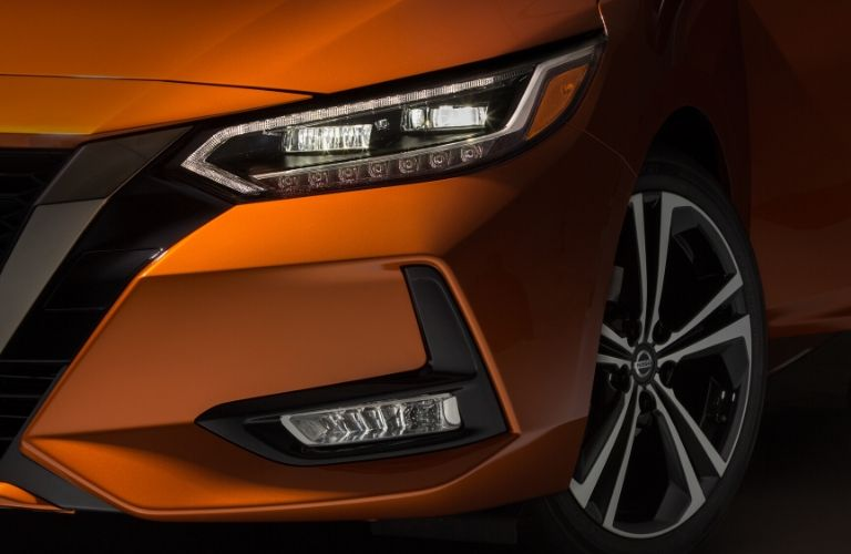 Closeup exterior view of the driver's side headlight on an orange 2020 Nissan Sentra