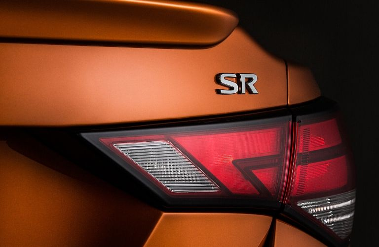 Closeup view of the passenger's side rear taillight and SR badge on an orange 2020 Nissan Sentra