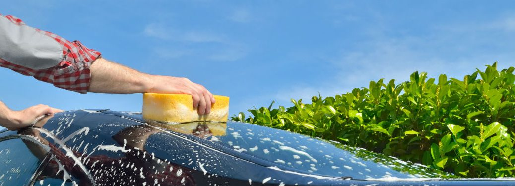 washing a car with a yellow sponge