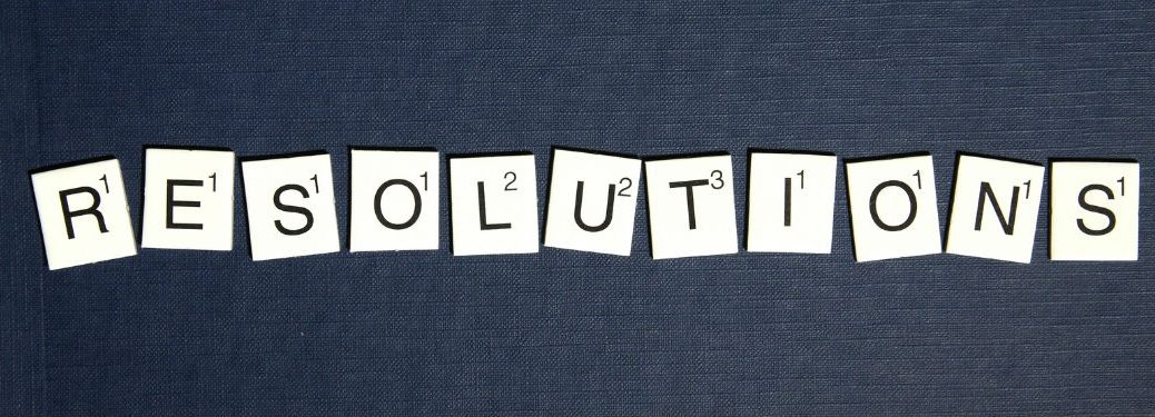 Resolutions spelled out with scrabble letters on denim blue background