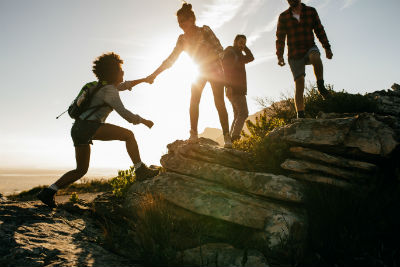 group of four people climbing up mountain